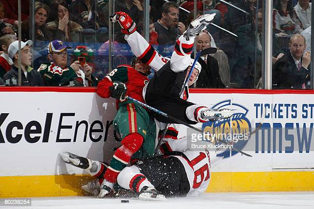 Sergei Brylin and Dainius Zubrus of the New Jersey Devils collide with Steve Kelly of the Minnesota Wild during the game at Xcel Energy Center on...