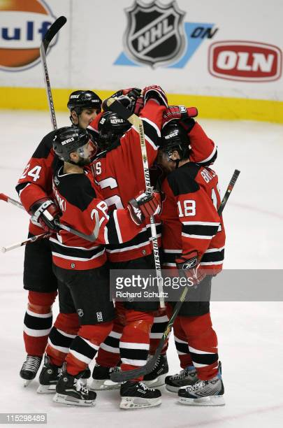 Sergei Brylin of the New Jersey Devils is congratulated by teammates after scoring a goal against the Carolina Hurricanes during the first period of...