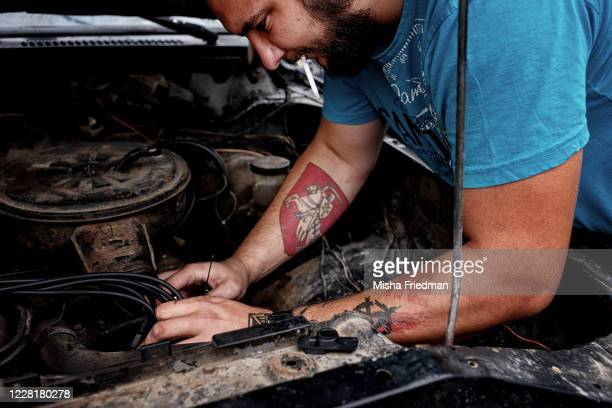 Sergei Dylevsky fixes his car before heading to a questioning by investigators on August 21, 2020 in Minsk, Belarus. After witnessing the injuries...