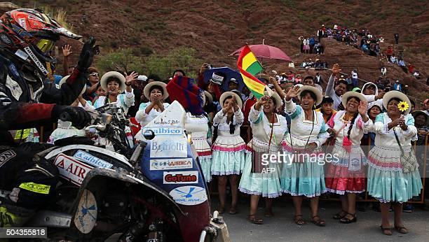 TOPSHOT Sergei Karyakin of Russia rides his Yamaha quad as Bolivian women cheer during the Stage 7 of the Dakar 2016 between Uyuni in Bolivia and...