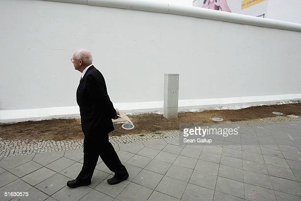 Sergei Khrushchev son of former Soviet leader Nikita Khrushchev walks past a rebuilt section of the Berlin Wall and crosses that commemorate its...