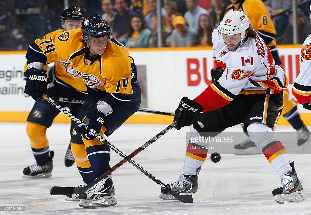 Sergei Kostitsyn #74 of the Nashville Predators skates against Maxwell Reinhart #59 of the Calgary Flames during an NHL game at the Bridgestone Arena on April 23, 2013 in Nashville, Tennessee.