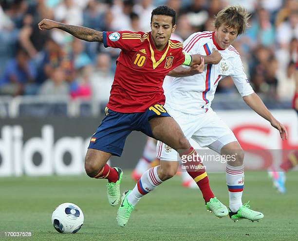 Sergei Petrov of Russia challenges Thiago Alcantara of Spain during the UEFA European U21 Championships Group B match between Spain and Russia at...