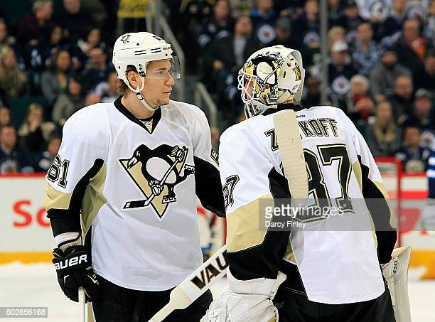 Sergei Plotnikov and goaltender Jeff Zatkoff of the Pittsburgh Penguins chat during a first period stoppage of play against the Winnipeg Jets at the...