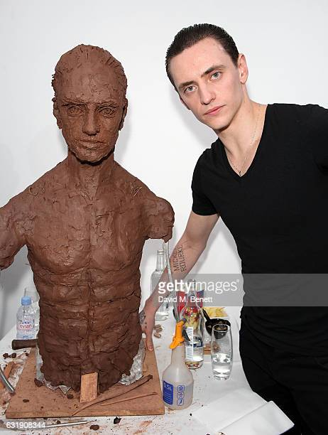 Sergei Polunin poses next to the sculpture while Artist Frances Segelman sculpts dancer Sergei Polunin at The Hospital Club Gallery on January 17,...