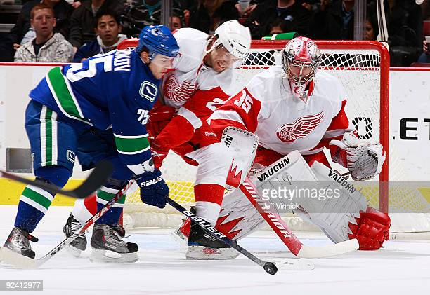 Sergei Shirokov of the Vancouver Canucks battles Brad Stuart of the Detroit Red Wings in front of the net as teammate Jimmy Howard gets into position...