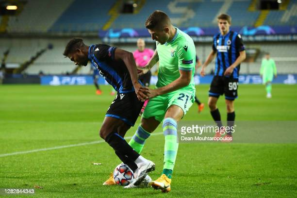 Sergej Milinkovic-Savic of SS Lazio battles for the ball with Emmanuel Bonaventure Dennis of Club Brugge KV during the UEFA Champions League Group F...
