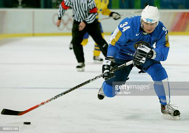 Sergey Alexandrov of Kazakhstan controls the puck during the men's ice hockey Preliminary Round Group B match between Kazakhstan and Sweden during...