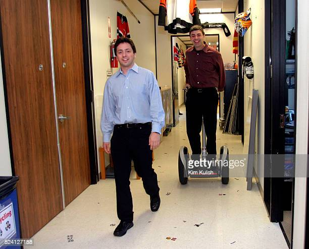Sergey Brin CoFounder and President Technology walks while Larry Page CoFounder and President Products rides a Segway Human Transporter through the...