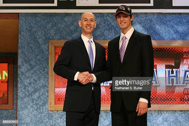 Sergey Gladyr shakes hands with NBA Deputy Commissioner Adam Silver after being selected forty ninth by the Atlanta Hawks during the 2009 NBA Draft...