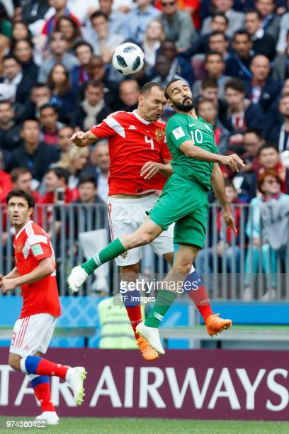Sergey Ignashevich of Russia and Mohammed AlSahlawi of Saudi Arabia battle for the ball during the 2018 FIFA World Cup Russia group A match between...