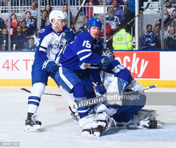 Sergey Kalinin of the Toronto Marlies runs into traffic with Slater Koekkoek and goalie Mike McKenna of the Syracuse Crunch during game 6 action in...