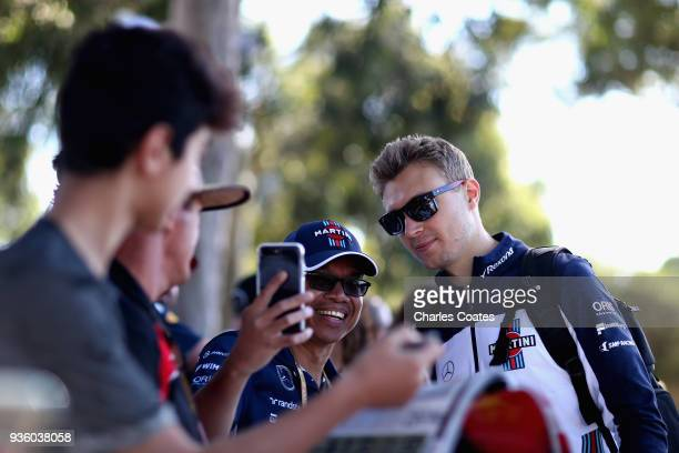 Sergey Sirotkin of Russia and Williams arrives at the circuit and poses for a photo with a fan during previews ahead of the Australian Formula One...