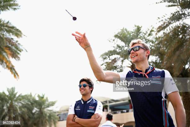 Sergey Sirotkin of Russia and Williams plays darts in the Paddock during previews ahead of the Bahrain Formula One Grand Prix at Bahrain...