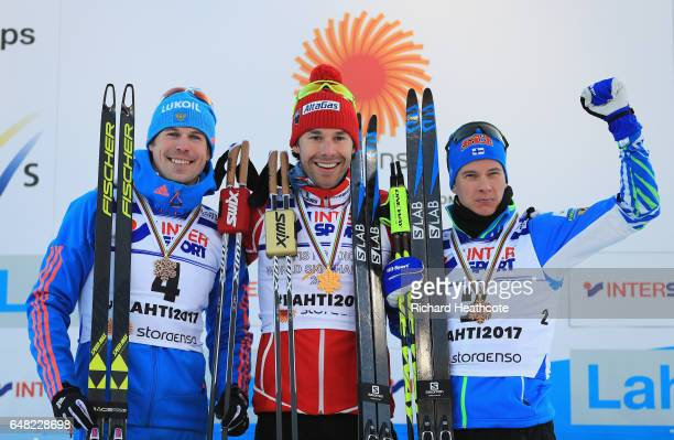 Sergey Ustiugov of Russia Alex Harvey of Canada and Matti Heikkinen of Finland pose for the media during the flower ceromeny after in the Men's Cross...