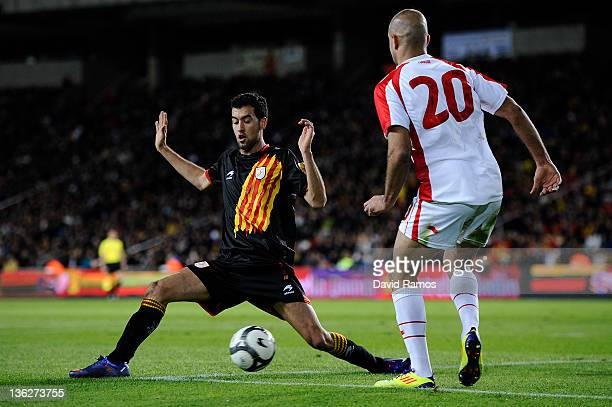 Sergi Busquets of Catalonia duels for the ball with Aymen Abdennoun during an International Friendly match between Catalonia and Tunisia at Estadi...