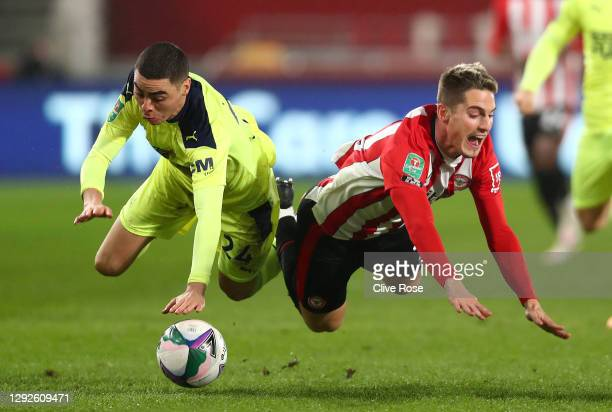 Sergi Canos of Brentford and Miguel Almiron of Newcastle United come together during the Carabao Cup Quarter Final match between Brentford and...