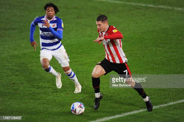 Sergi Canos of Brentford runs with the ball under pressure from Michael Olise of Reading during the Sky Bet Championship match between Brentford and...