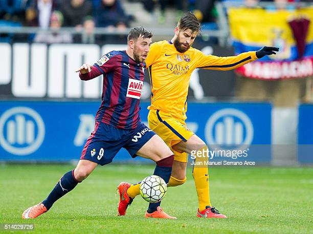 Sergi Enrich of SD Eibar duels for the ball with Gerard Pique of FC Barcelona during the La Liga match between SD Eibar and FC Barcelona at Ipurua...
