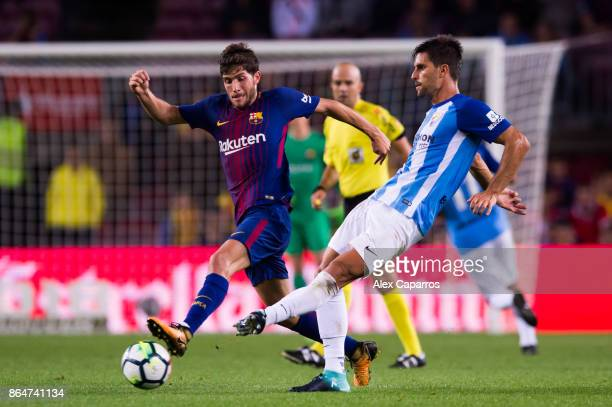 Sergi Roberto of FC Barcelona and Adrian Gonzalez of Malaga CF compete for the ball during the La Liga match between Barcelona and Malaga at Camp Nou...