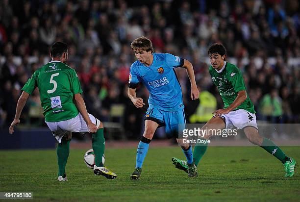 Sergi Samper of FC Barcelona flicks the ball past Javi Sanchez of FC Villanovense during the Copa del Rey Last of 16 First Leg match between CF...