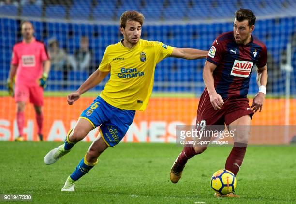 Sergi Samper of Las Palmas competes for the ball with Sergi Enrich Ametller of Eibar during the La Liga match between Las Palmas and Eibar at Estadio...