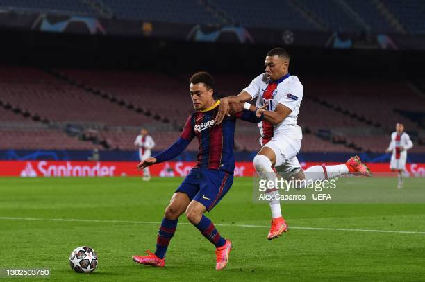 Sergino Dest of FC Barcelona and Kylian Mbappe of Paris Saint-Germain battle for possession during the UEFA Champions League Round of 16 match...