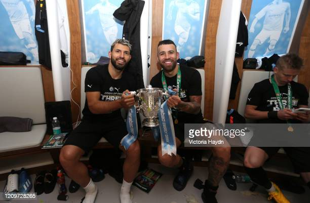Sergio Aguero and Nicolas Otamendi of Manchester City pose with the trophy in the dressing room after the Carabao Cup Final between Aston Villa and...
