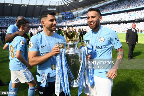 Sergio Aguero and Nicolas Otamendi with the Premier league trophy after the Premier League match between Manchester City and Huddersfield Town at...