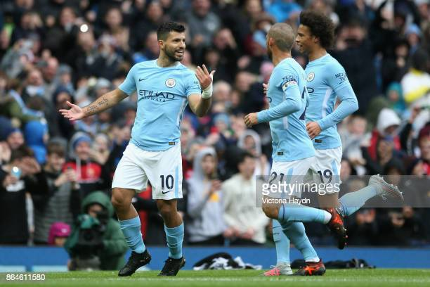 Sergio Aguero celebrates scoring his side's first goal with David Silva and Leroy Sane of Manchester City during the Premier League match between...