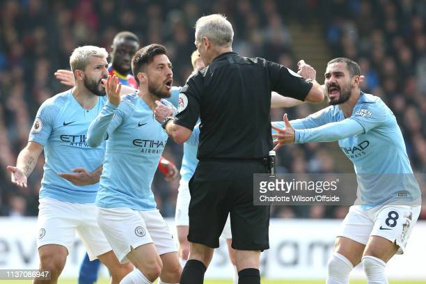 Sergio Aguero David Silva and Ilkay Gundogan of Man City argue with referee Martin Atkinson during the Premier League match between Crystal Palace...