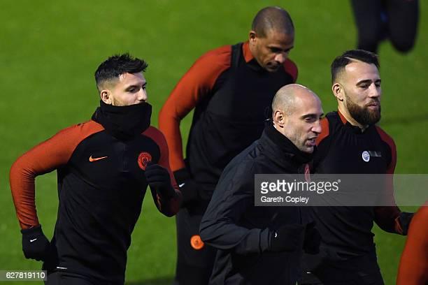 Sergio Aguero Fernando Pablo Zabaleta and Nicolas Otamendi of Manchester City run during a training session ahead of the UEFA Champions League group...