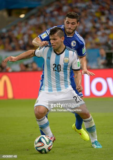 Sergio Aguero of Argentina challenged by Sead Kolasinac of BosniaHerzegovina during the 2014 FIFA World Cup Brazil Group F match between Argentina...
