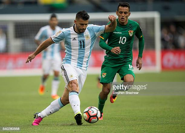 Sergio Aguero of Argentina dribbles the ball against Jhasmani Campos of Bolivia during a group D match between Argentina and Bolivia at CenturyLink...