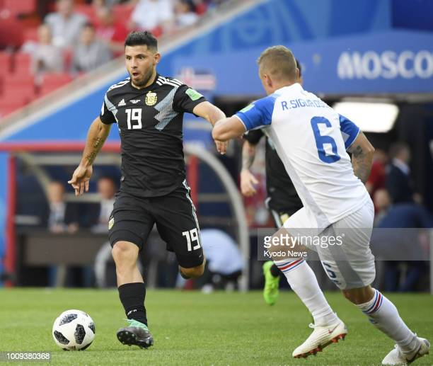 Sergio Aguero of Argentina dribbles the ball while being marked by Ragnar Sigurdsson of Iceland during the second half of a 11 draw in a World Cup...