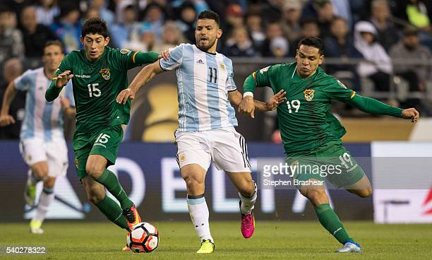 Sergio Aguero of Argentina is grabbed by Pedro Azogue of Bolivia and Carmelo Algaranaz during a group D match between Argentina and Bolivia at...