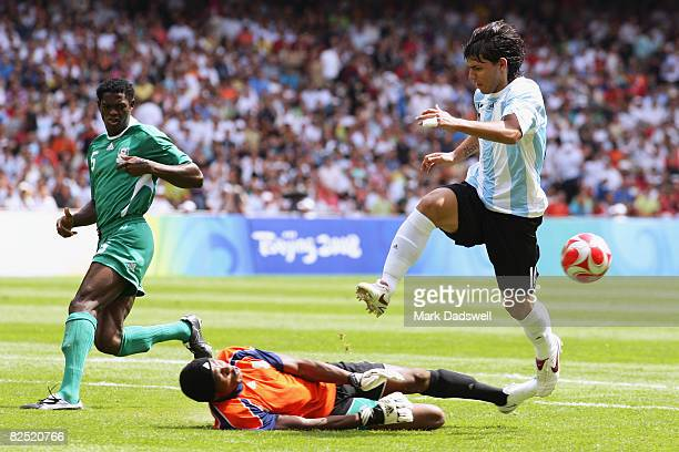 Sergio Aguero of Argentina jumps goalkeeper Ambrose Vanzekin of Nigeria in the Men's Gold Medal football match between Nigeria and Argentina at the...