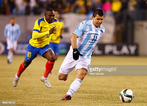 Sergio Aguero of Argentina moves the ball past Walter Ayovi of Ecuador in the second half during an international friendly at Metlife Stadium on...