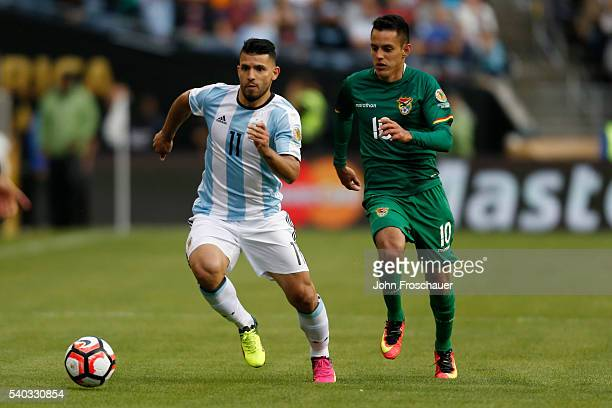 Sergio Aguero of Argentina runs after the ball while followed by Jhasmani Campos of Bolivia during a group D match between Argentina and Bolivia at...