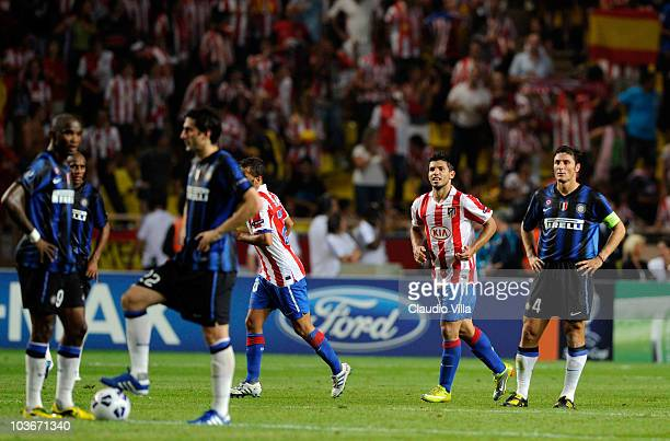 Sergio Aguero of Atletico celebrates after scoring his team's second goal as Javier Zanetti of Inter shows his dejection during the UEFA Super Cup...