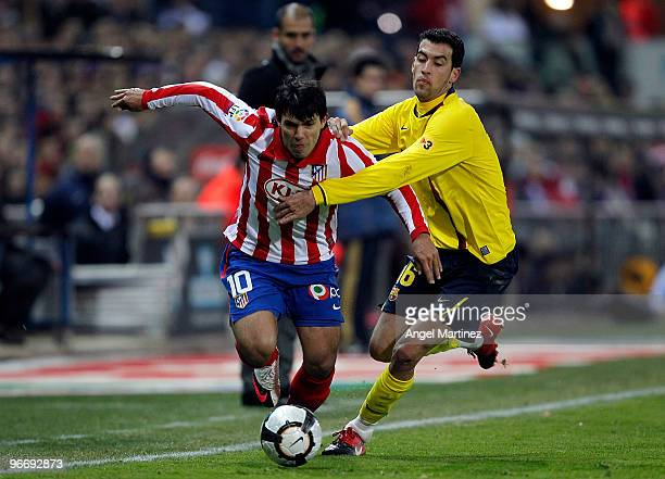 Sergio Aguero of Atletico Madrid duels for the ball with Sergio Busquets of Barcelona during the La Liga match between Atletico Madrid and Barcelona...