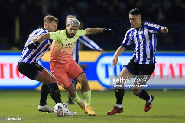 Sergio Aguero of Man City battles with Tom Lees of Sheff Wed and Joey Pelupessy of Sheff Wed during the FA Cup Fifth Round match between Sheffield...