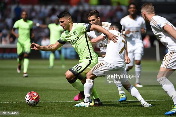 Sergio Aguero of Manchester City and Leon Britton of Swansea City compete for the ball during the Barclays Premier League match between Swansea City...