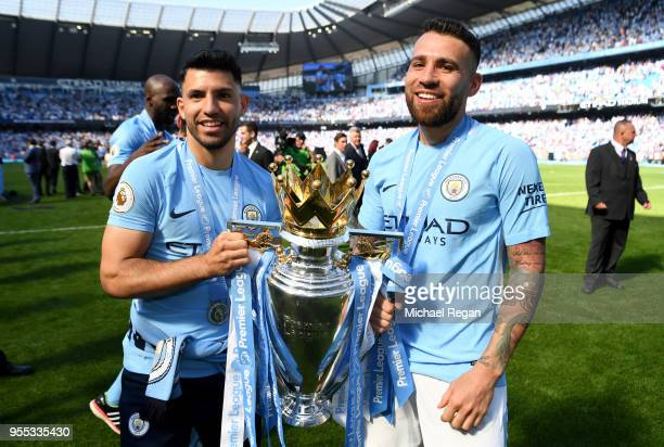Sergio Aguero of Manchester City and Nicolas Otamendi of Manchester City celebrate with The Premier League Trophy after the Premier League match...