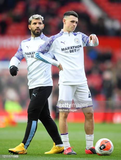 Sergio Aguero of Manchester City and Phil Foden of Manchester City warm up ahead of the Premier League match between Manchester United and Manchester...
