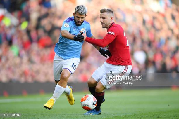 Sergio Aguero of Manchester City battles for possession with Luke Shaw of Manchester United during the Premier League match between Manchester United...