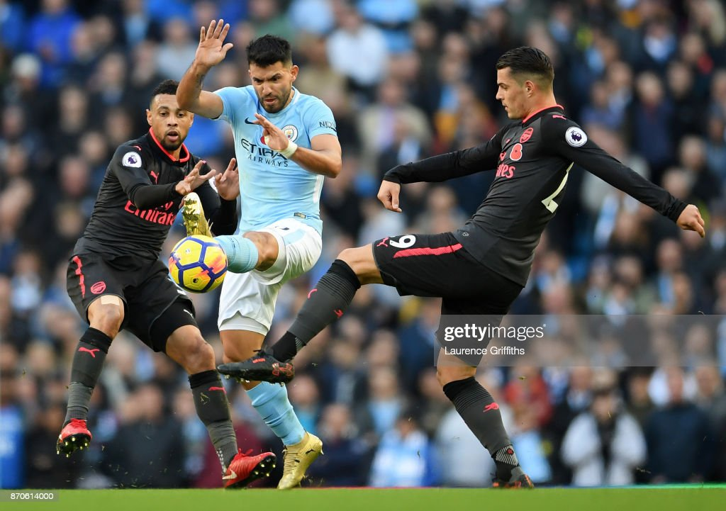 Sergio Aguero (c) of Manchester City battles for the ball with Francis Coquelin (l) and Granit Xhaka (r) of Arsenal during the Premier League match between Manchester City and Arsenal at Etihad Stadium on November 5, 2017 in Manchester, England.
