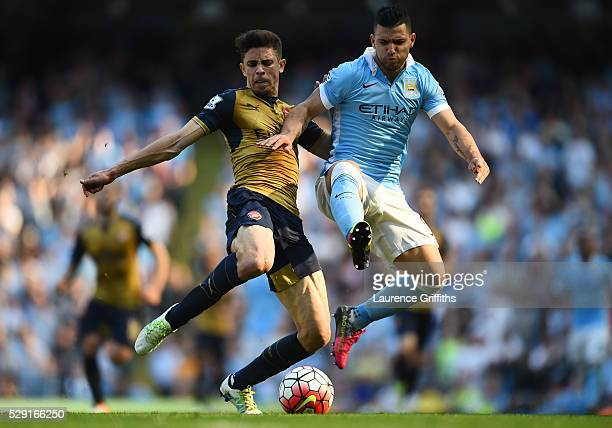 Sergio Aguero of Manchester City battles for the ball with Gabriel Paulista of Arsenal during the Barclays Premier League match between Manchester...
