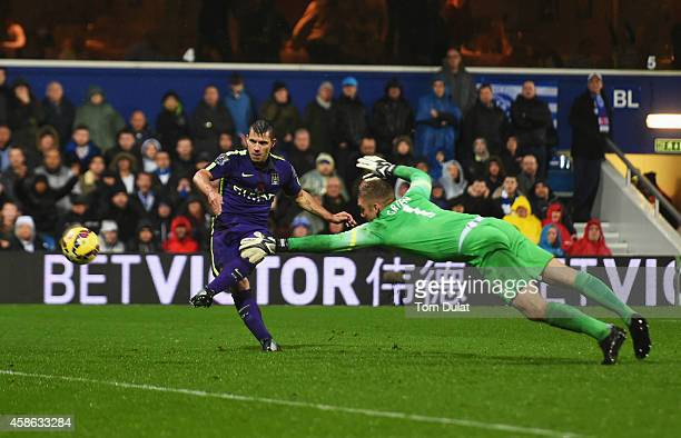 Sergio Aguero of Manchester City beats goalkeeper Robert Green of QPR to score their second goal during the Barclays Premier League match between...