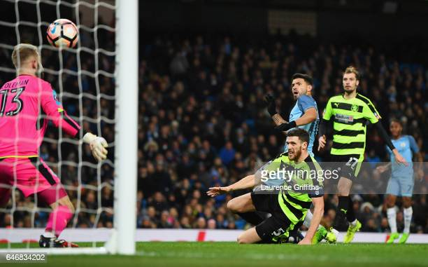 Sergio Aguero of Manchester City beats Mark Hudson and goalkeeper Joel Coleman of Huddersfield Town as he scores their fourth goal during The...